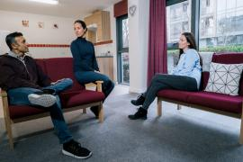 Three residents sat talking in the shared lounge area of their en-suite accommodation