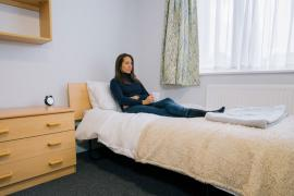 A woman sat on her bed within her Grantchester House bedroom