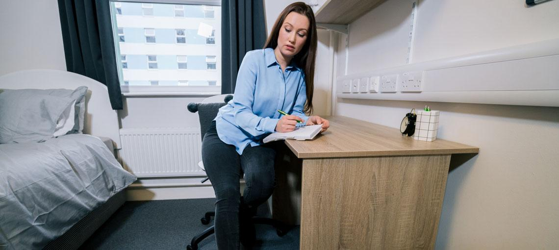 Woman sat at her bedroom desk making notes