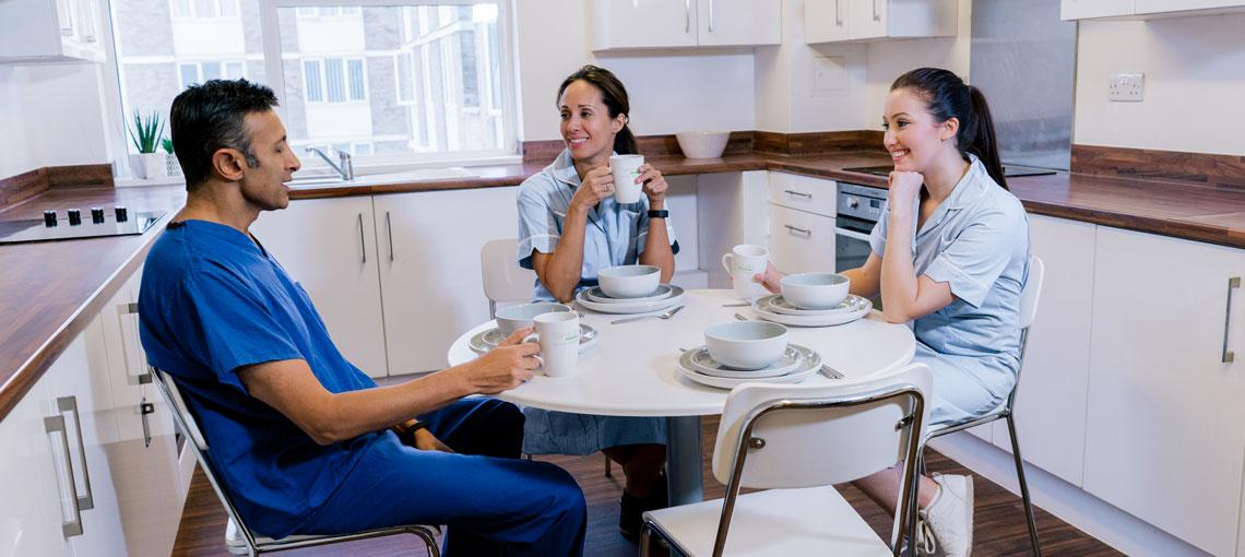 Three residents in their nursing uniforms sat in the kitchen talking.